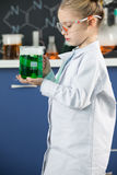 Girl wearing lab coat and protective glasses holding flask with green reagent Royalty Free Stock Photography