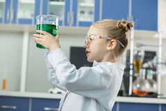 Girl wearing lab coat and protective glasses holding flask with green reagent Stock Photography