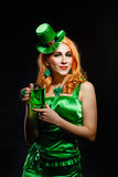 Girl wearing leprechaun. Red hair girl in Saint Patrick's Day leprechaun party hat having fun, holding a mug of ale Stock Photography