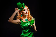 Girl wearing leprechaun. Red hair girl in Saint Patrick's Day leprechaun party hat having fun, holding a mug of ale Stock Images
