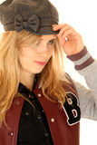 Girl wearing a letterman jacket while adjusting her hat Royalty Free Stock Photos