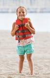 Girl wearing life jacket at beach royalty free stock photos