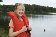 Girl Wearing Life Jacket By Lake Royalty Free Stock Photos