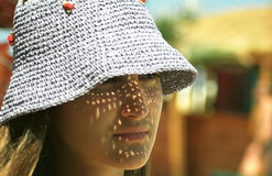 Girl Wearing Light Sun Hat. A young girl on a beach wearing a loose-knit sun hat as the sunlight filters through the had and makes an interesting pattern on her Royalty Free Stock Image