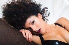 Girl wearing lingerie lying sideways on sofa Stock Images