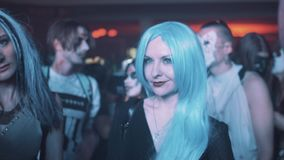 Girl wearing long blue hair wig in crowd of people at night club halloween party. Flashing white light stock footage