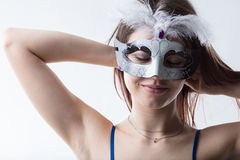 Girl wearing a mask ready for the party. Young woman wearing a mask ready for something she`s imagining to happen stock photography