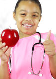 An apple a day keeps the doctor away. Girl wearing medical stethoscope expresses the old adage that an apple a day keeps you healthy. Focus on the eyes of the Stock Images