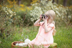 Girl Wearing Orange Dress Holding Camera Sitting on Green Grass during Day Time Stock Photo