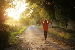 Girl Wearing Orange Long Sleeve Shirt and Black Pants Walking Alone Along Road Facing the Sun Royalty Free Stock Images