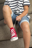Girl wearing a pair of red sneakers Stock Photos