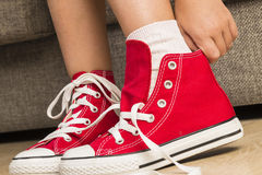 Girl wearing a pair of red sneakers Stock Images