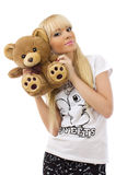 Girl wearing pajamas embraces teddy bear Royalty Free Stock Image