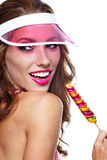 Girl wearing plastic cap holding lollipop Royalty Free Stock Images