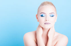 Girl wearing professional make-up posing with eyes closed. Isolated on blue background with copy text space Stock Photo