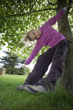 Girl (7-9) wearing purple top and combat trousers, swinging from branch in garden, arms outstretched, head cocked, smiling, portra Stock Photography