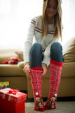 Girl wearing red christmas socks Stock Images
