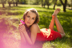 Girl wearing red dress lying on the grass Stock Photos