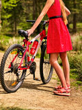 Girl wearing red dress rides bicycle in autumn park. Royalty Free Stock Photography