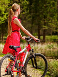 Girl wearing red dress rides bicycle in park. Royalty Free Stock Images
