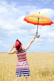 Girl wearing red hat rising umbrella and standing Stock Image