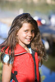 Girl (7-9) wearing red life jacket, smiling, portrait Stock Images
