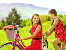 Girl wearing red polka dots dress rides bicycle into park. Royalty Free Stock Photo