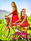 Girl wearing red polka dots dress rides bicycle into park. Royalty Free Stock Images
