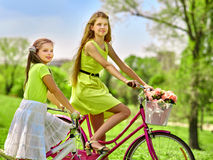 Girl wearing red polka dots dress rides bicycle into park. Stock Image