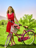 Girl wearing red polka dots dress rides bicycle into park. Stock Images