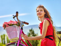 Girl wearing red polka dots dress rides bicycle into park. Royalty Free Stock Image