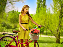 Girl wearing red polka dots dress rides bicycle into park. Bikes bicycle girl. Teenager girl wearing yellow polka dots dress looking dreamily keeps bicycle with royalty free stock photo