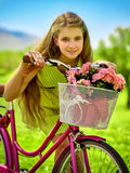 Girl wearing red polka dots dress rides bicycle into park. Bikes bicycle girl. Teenager girl wearing yellow polka dots dress looking dreamily keeps bicycle with royalty free stock photography