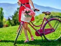 Girl wearing red polka dots dress rides bicycle into park. Body part bicycle girl wearing red polka dots dress rides bicycle into park stock photo