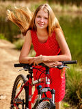 Girl wearing red polka dots dress rides bicycle into park. Royalty Free Stock Photos