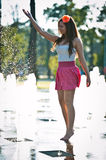 girl wearing red skirt playing water fountain Royalty Free Stock Image
