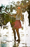 Girl wearing red skirt playing water fountain Stock Photo