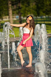 Girl wearing red skirt playing water fountain Royalty Free Stock Photography