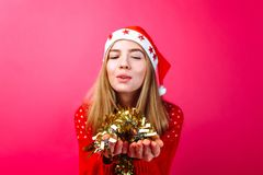A girl wearing a red sweater and a Santa hat holds tinsel in her hand and blows on it, on a red background stock photos