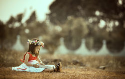 Girl Wearing Red Top White Skirt and Flower Headdress Sitting on Ground Royalty Free Stock Images