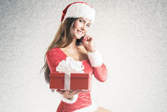 Girl wearing santa claus clothes with christmas gift stock photos