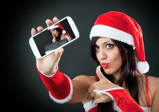 Girl wearing santa claus clothes with smartphone Stock Photography