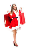 Girl wearing Santa Claus costume holding shopping bags Stock Photography