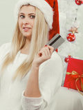 Girl wearing santa claus hat holds credit card for buying Royalty Free Stock Photo