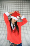 Girl wearing Santa hat. With her hands over her head Royalty Free Stock Image