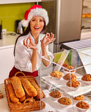 Girl wearing santa hat seller sells bread in store Royalty Free Stock Images