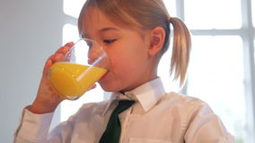 Girl Wearing School Uniform Drinking Glass Of Orange Juice stock video