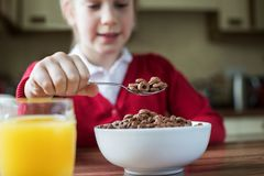 Girl Wearing School Uniform Eating Bowl Of Sugary Breakfast Cere. Al Royalty Free Stock Images