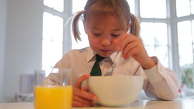 Girl Wearing School Uniform Eating Breakfast Cereal. Girl wearing school uniform sitting at kitchen table and eating breakfast.Shot on Canon 5d Mk2 with a frame stock footage