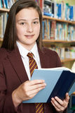 Girl Wearing School Uniform Reading Book In Library Royalty Free Stock Photo